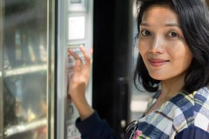 Woman chooses goods from vending machine
